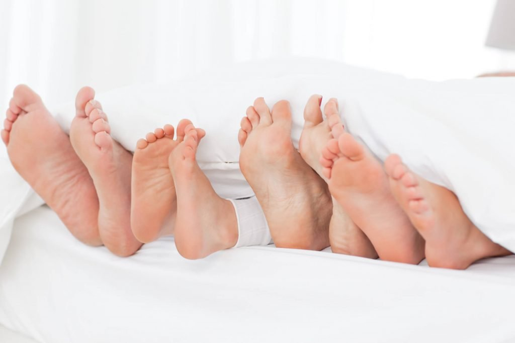 family of feet in bed