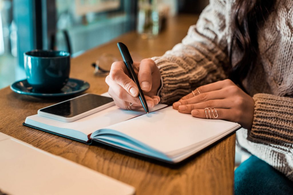 woman writing in notepad, with phone, and cup of tea