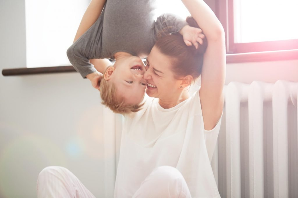 happy mom with young son hanging upside down