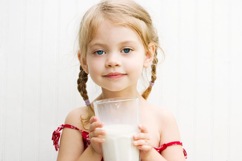 toddler girl drinking milk from a glass, weaned from breastfeeding