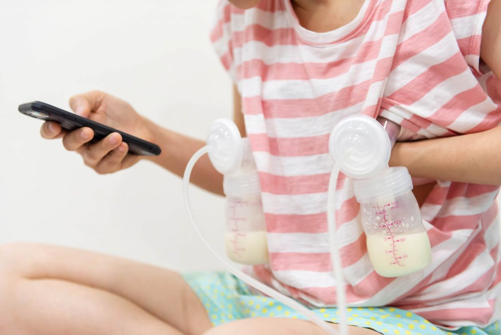 woman pumping breast milk and looking at phone instead of breastfeeding