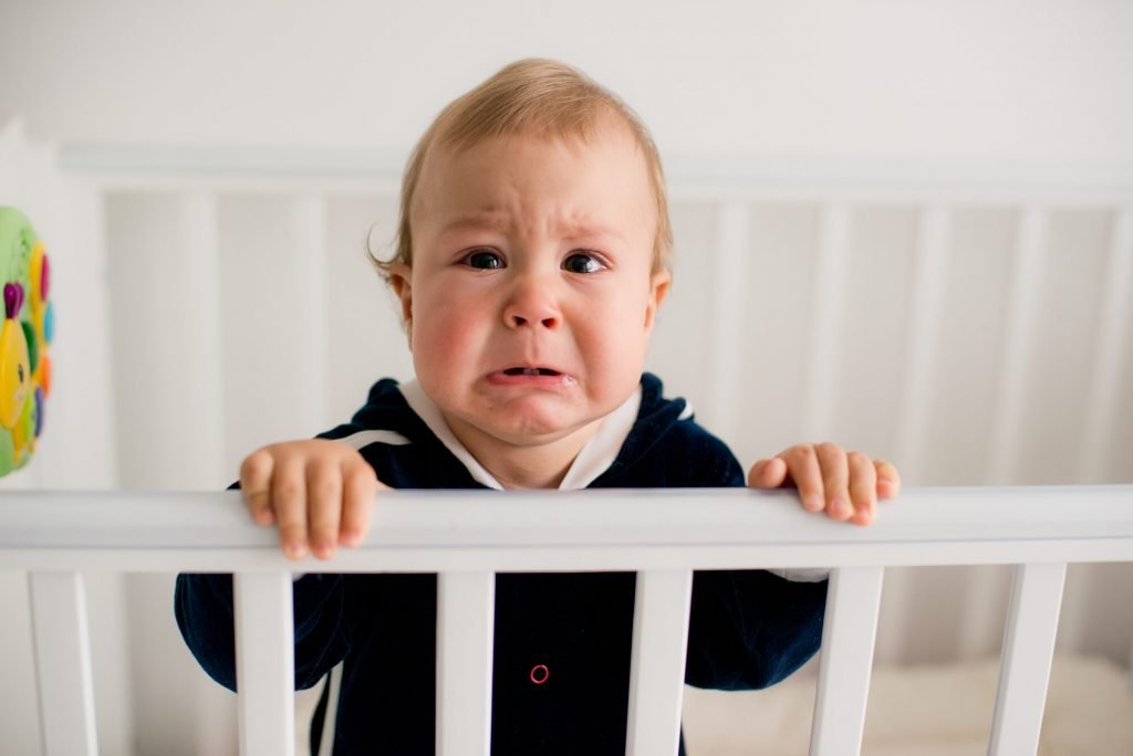 upset baby in crib