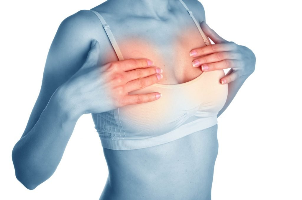 woman clutching painful breasts