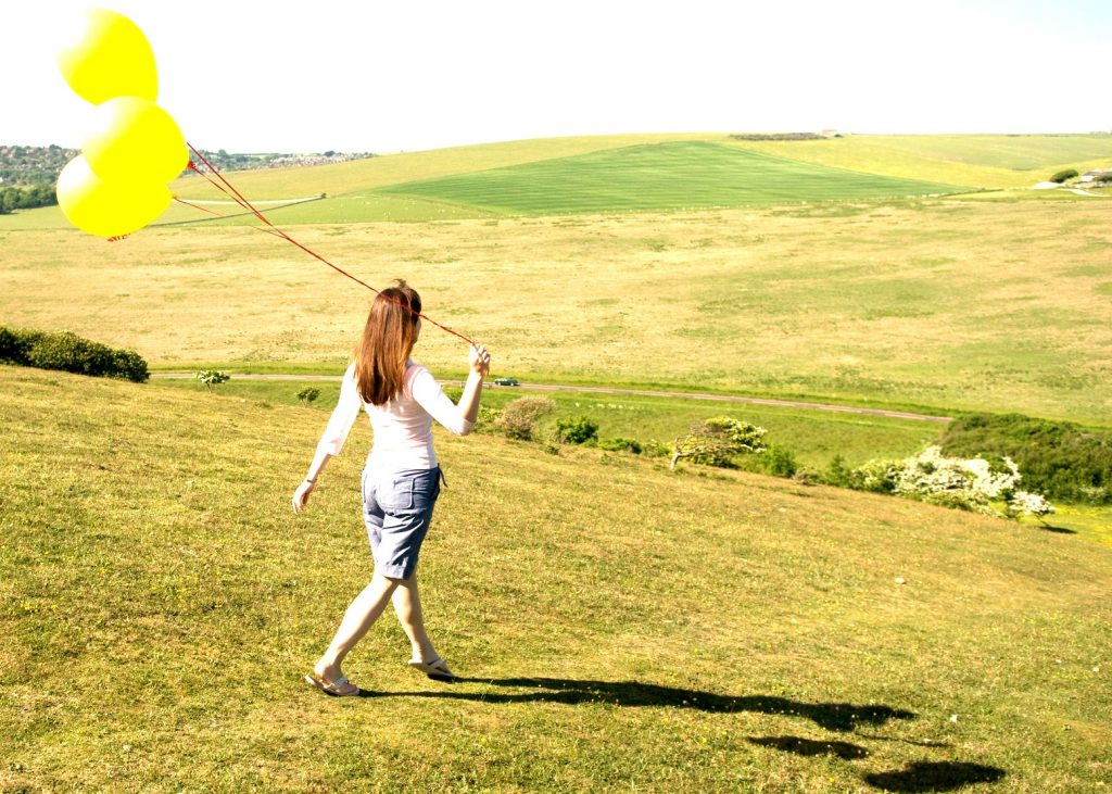 happy woman from behind walking down a hill with 3 yellow balloons trailing behind