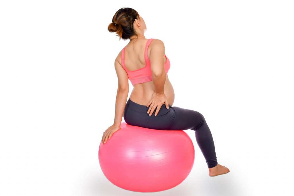 pregnant woman sitting on exercise ball to prepare for labor and delivery