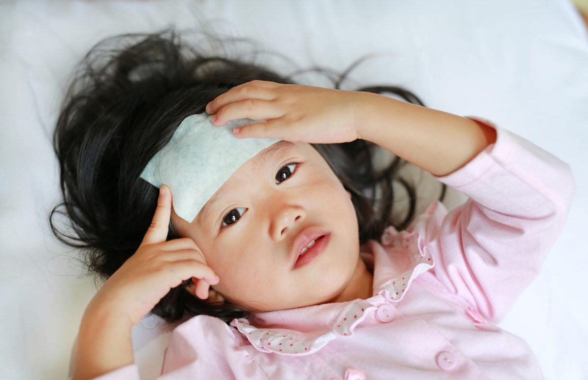 asian baby girl laying down sick with fever and cool rag on forehead