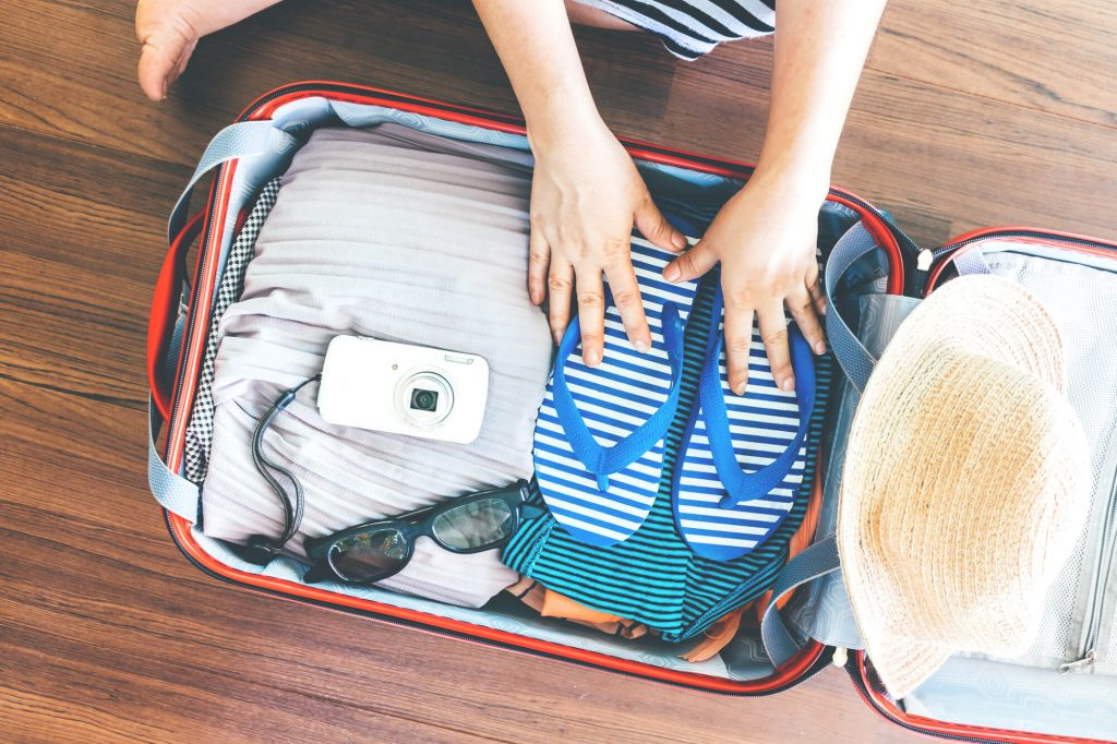 woman packing for the beach-weather appropriate tips for traveling with babies