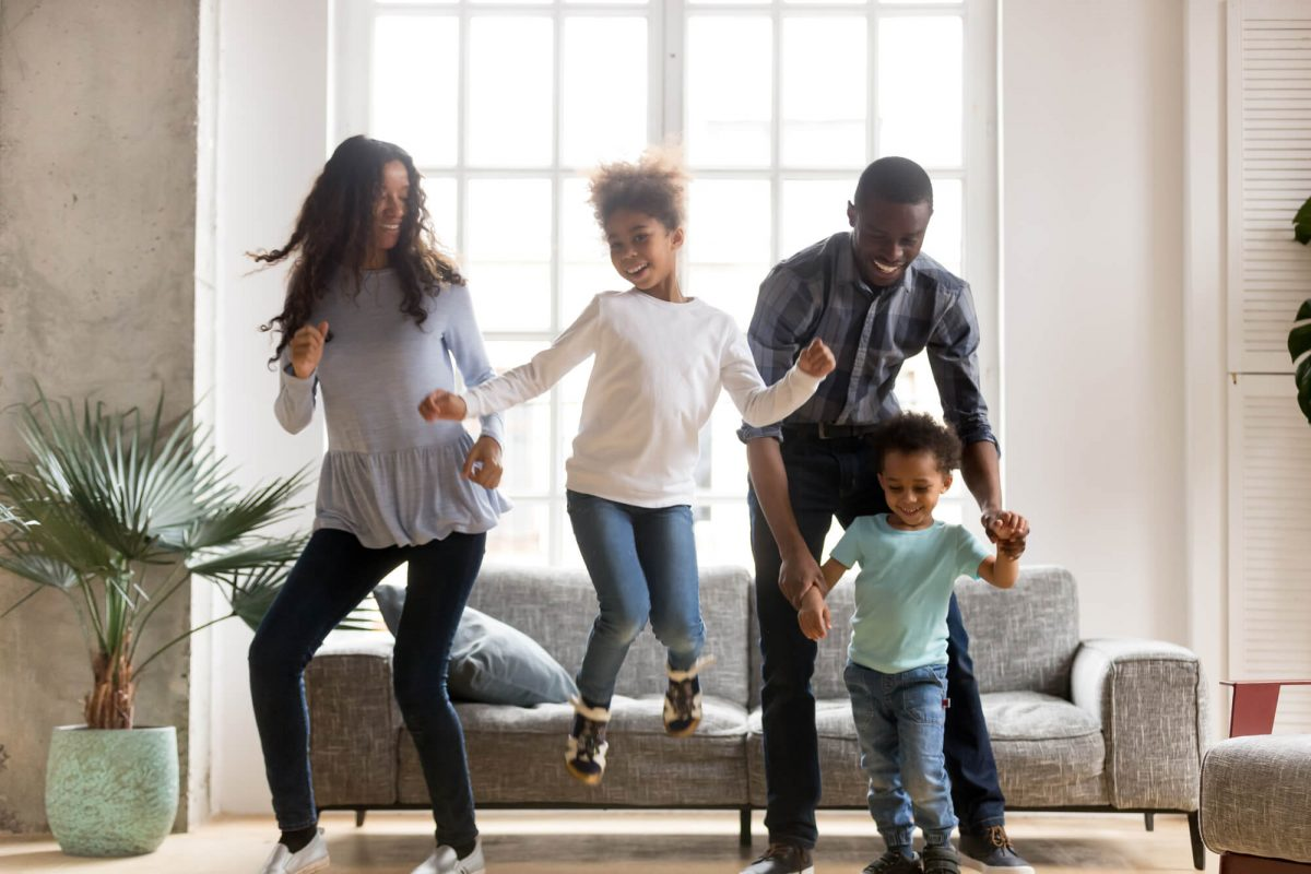 family of 4 listening to kid friendly songs, dancing and having fun together